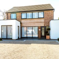 Front elevation transformed with aluminium windows timber cladding and white render