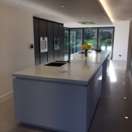 Long kitchen island with polished plaster wall